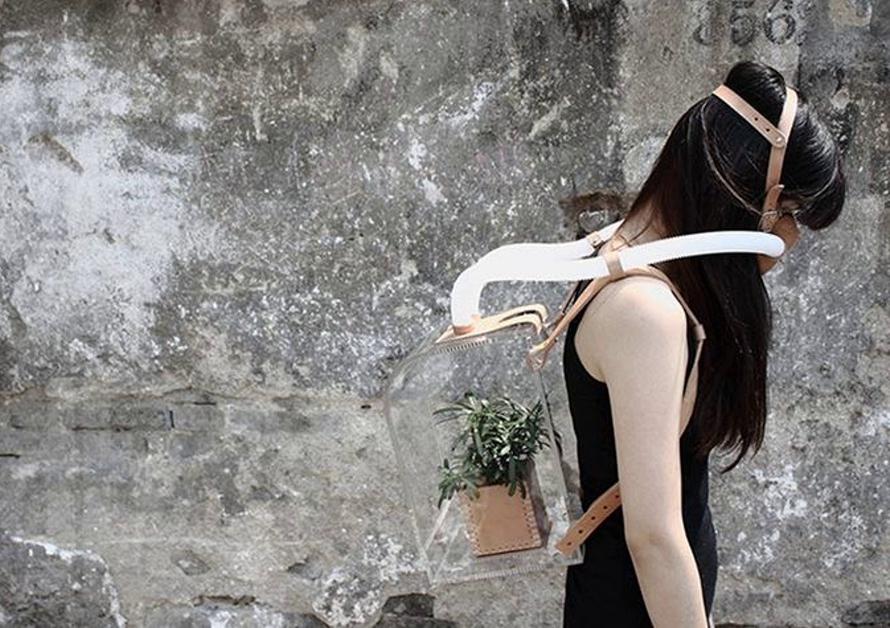 Meisje uit de toekomst met zuurstofmasker op haar gezicht en met een doorzichtige tank op haar rug waar een plant inzit zodat ze schone lucht kan inademen